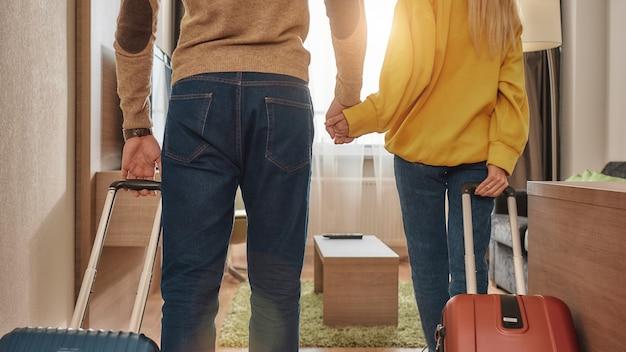 Bijgesneden portret van jonge man en vrouw in vrijetijdskleding met koffers die hun kamer in een hotel binnenkomen. ze houden elkaars hand vast. samen reizen concept. horizontaal schot. achteraanzicht