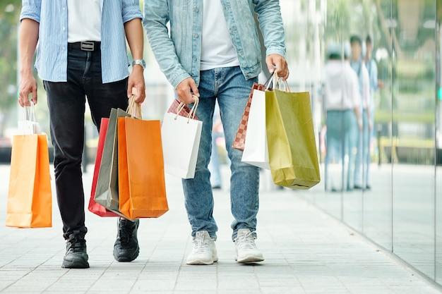 Bijgesneden portret van jonge mannen met veel kleurrijke boodschappentassen die op straat lopen