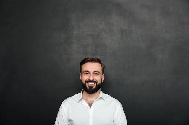 Bijgesneden portret van jonge vrolijke man in het witte shirt poseren op camera met brede glimlach, geïsoleerd over donkere grijze muur