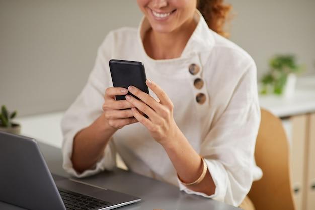 Bijgesneden portret van lachende jonge vrouw met behulp van smartphone op werkplek terwijl u geniet van werk vanuit huis, kopie ruimte