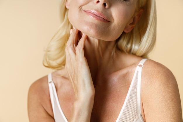 Bijgesneden portret van mooie rijpe blonde vrouw in wit ondergoed glimlachend haar nek aan te raken