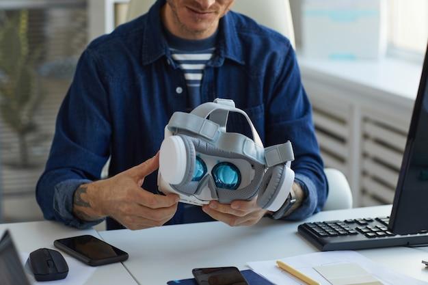 Bijgesneden portret van onherkenbare it-ontwikkelaar die vr-headset vasthoudt terwijl hij aan augmenter reality-toepassingen werkt, kopieer ruimte