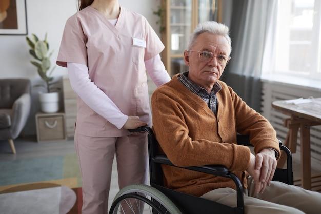 Bijgesneden portret van senior man in rolstoel kijkend naar camera met onherkenbare verpleegster die hem helpt, kopieer ruimte