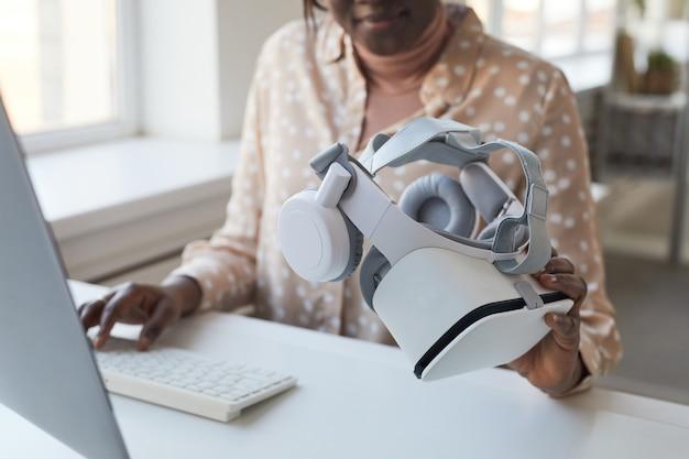 Bijgesneden portret van vrouwelijke it-ontwikkelaar die een vr-headset vasthoudt terwijl ze aan augmented reality-games en -software werkt, kopieer ruimte