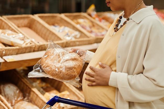 Bijgesneden portret van zwangere afro-amerikaanse vrouw die vers brood koopt terwijl ze boodschappen doet in de supermarkt, kopieer ruimte