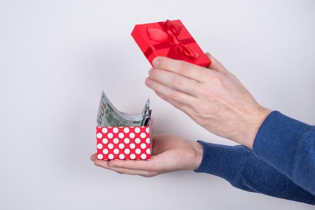 Bijgesneden profielfoto aan de zijkant van de handen van de student met uitgepakt rood klein pakketje vol geld geïsoleerd grijze achtergrond