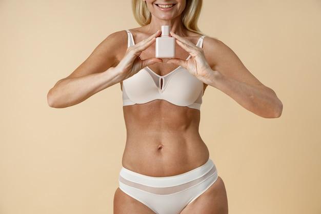 Bijgesneden rijpe blonde vrouw in ondergoed met fit lichaam glimlachend in de camera en weergegeven: witte bottle