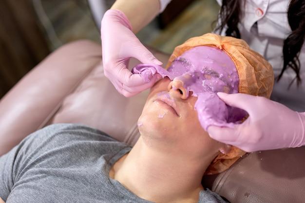 Bijgesneden schoonheid arts verwijdert paars huidmasker van mannelijke patiënt gezicht, mannelijke zorgt voor de huid, krijgt schoonheidsprocedures in salon