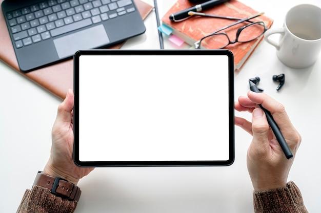 Bijgesneden schot bovenaanzicht van zakenman handen met behulp van tablet mockup op het witte bureau. mobiele telefoon met leeg scherm voor montage van grafische weergave