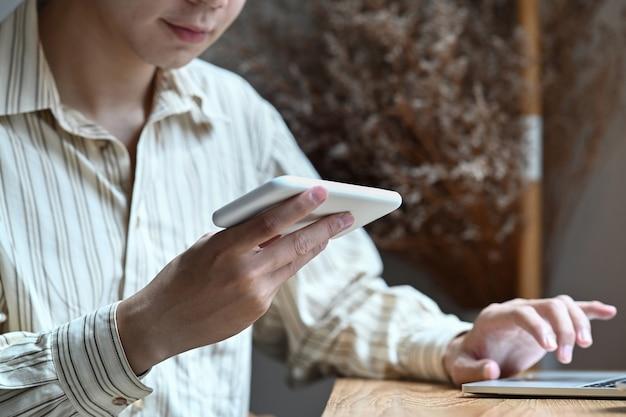 Bijgesneden schot glimlachende man met mobiele telefoon en werken met laptopcomputer.
