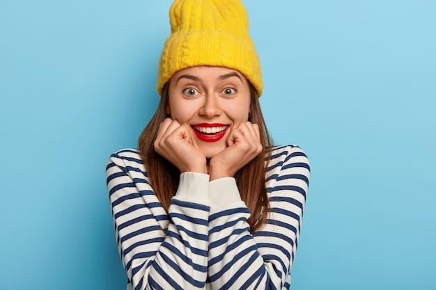 Bijgesneden schot van aangenaam uitziende jonge vrouw glimlacht breed, heeft witte tanden, draagt rode lippenstift, houdt handen onder de kin, draagt gele hoed, gestreepte zeeman trui, grijnst vreugdevol, heeft geweldige dag