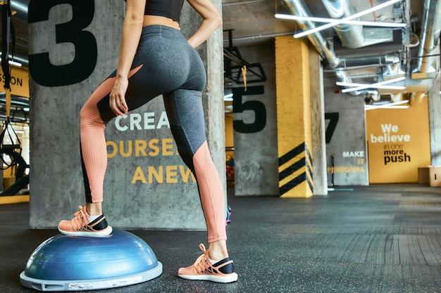 Bijgesneden schot van atletische vrouw in sportkleding staande op crossfit gym. training, training, actieve en gezonde levensstijl