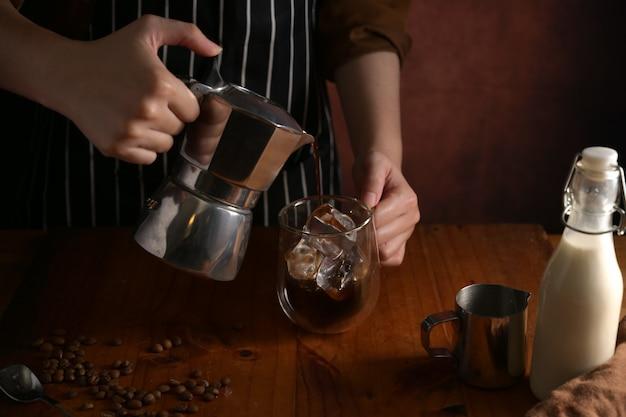 Bijgesneden schot van barista koffie gieten in beker met ijs op houten teller bar in coffeeshop