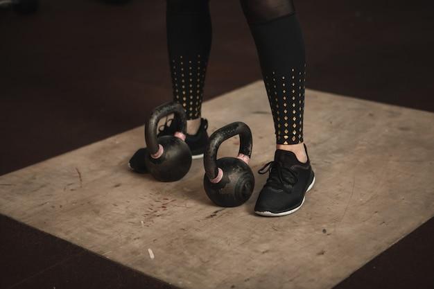 Bijgesneden schot van benen van vrouwelijke atleet die zich dichtbij twee kettlebells bevinden