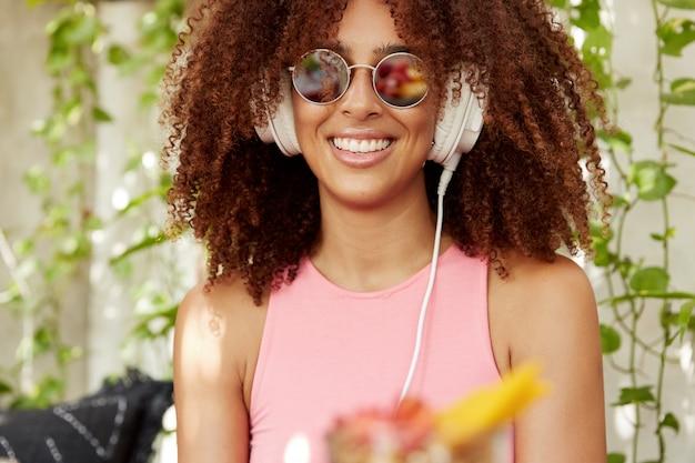 Bijgesneden schot van blije donkere vrouw met borstelige afro kapsel luistert favoriete afspeellijst in hoofdtelefoons, in goed humeur, modieuze zonnebril en roze t-shirt draagt, heeft stralende glimlach