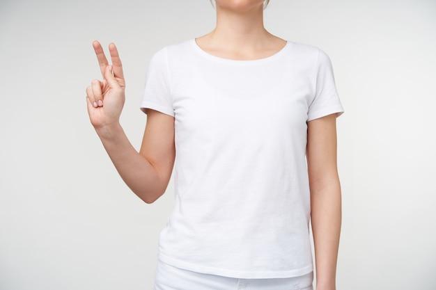Bijgesneden schot van de hand van de jonge vrouw die wordt verhoogd terwijl lettel k wordt weergegeven met gebarentaal, geïsoleerd op witte achtergrond. menselijke handen en dove taalconcept