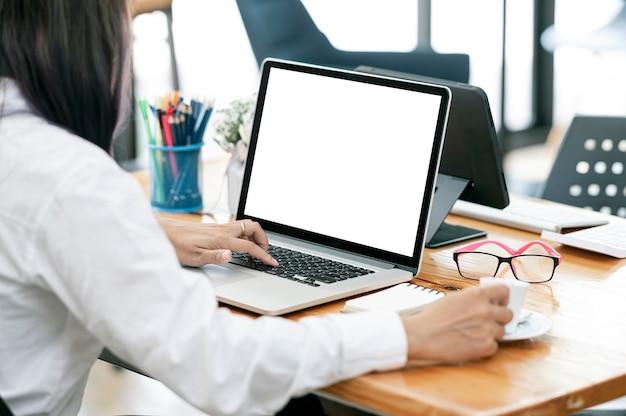 Bijgesneden schot van de hand van de vrouw die op een laptop met een leeg scherm werkt terwijl ze aan haar bureau zit.