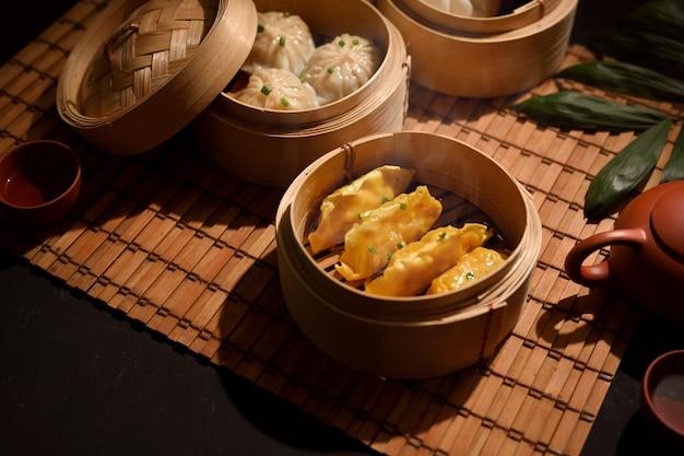 Bijgesneden schot van dimsum dumplings in bamboestoomboot op eettafel in chinees restaurant