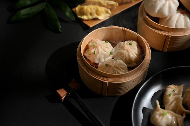 Bijgesneden schot van dimsum dumplings op bamboestoomboot op eettafel in chinees restaurant