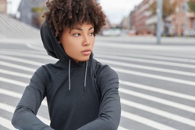 Bijgesneden schot van donkere huid hipster in sweatshirt, peinzend opzij kijkt, vormt tegen asfalt achtergrond