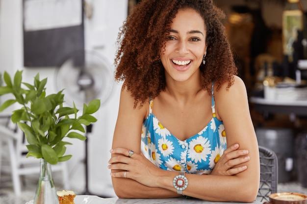 Bijgesneden schot van donkere huid lachende jonge vrouw met afro kapsel, gekleed in casual zomerkleding