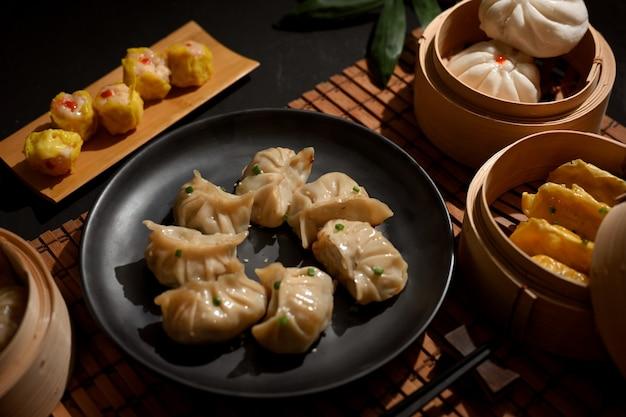 Bijgesneden schot van een bord en bamboe stoomboot van dimsum dumplings in chinees restaurant