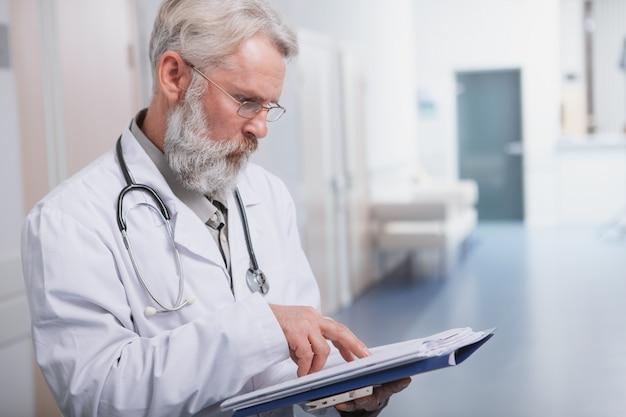 Bijgesneden schot van een senior mannelijke arts te concentreren, het lezen van medische documenten op zijn klembord, kopie ruimte