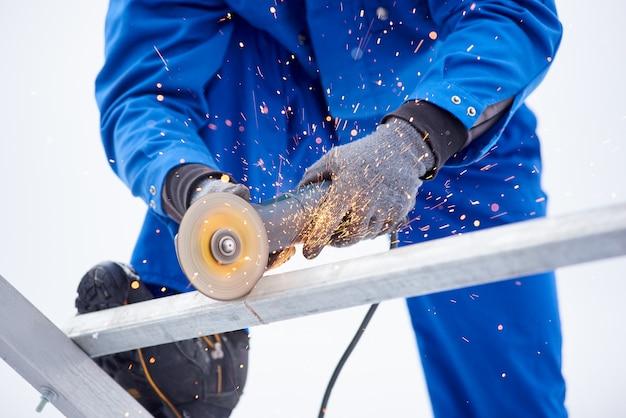 Bijgesneden schot van een technicus werknemer snijden staal op sonstruction site lassen constructeur werk beroep beroep baan ambacht metaal metaalbewerking industriële apparatuur gereedschappen.