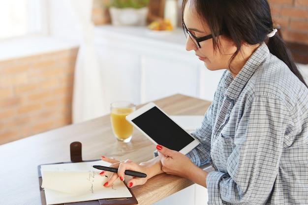 Bijgesneden schot van ernstige zakenvrouw beheert financiën, tabletcomputer houdt, kijkt aandachtig in notitieblok