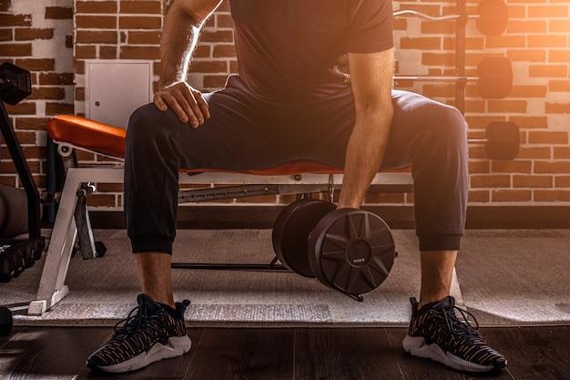 Bijgesneden schot van fitness man doen concentratie krullen oefening uit te werken met halter in de sportschool.