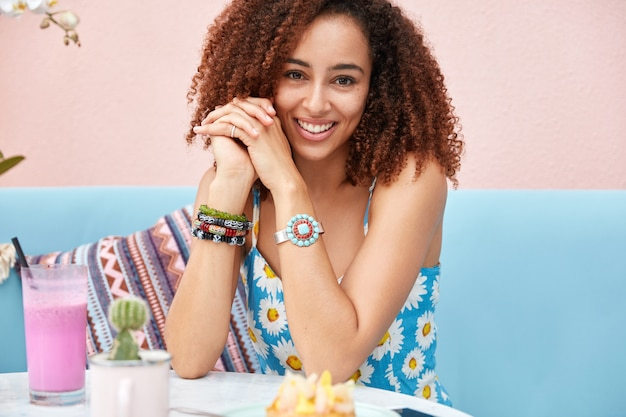Bijgesneden schot van goed uitziende ontspannen afro-amerikaanse vrouw besteedt vrije tijd met vrienden in café, drinkt vers fruit milkshake