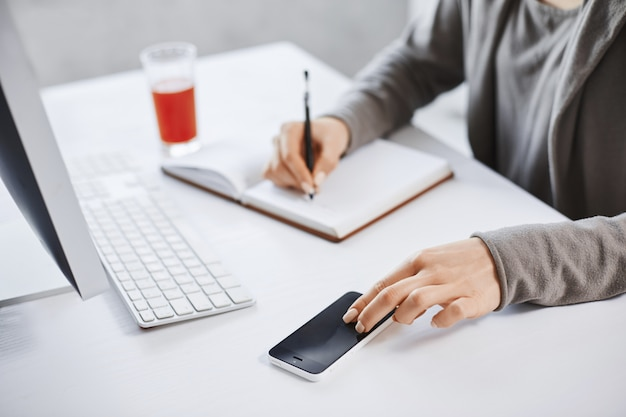 Bijgesneden schot van handen opschrijven in notitieblok en smartphone aan te raken. werknemer die op kantoor werkt, post via de computer controleert en vers sap drinkt om energie te stimuleren. deadlines zijn dichtbij
