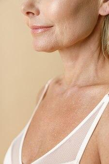 Bijgesneden schot van huid van rijpe blonde vrouw in witte beha glimlachend weg poseren geïsoleerd over beige