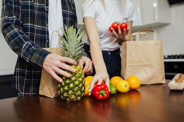 Bijgesneden schot van jong koppel tijdens het uitpakken van papieren zakken met verse groenten en fruit in de keuken