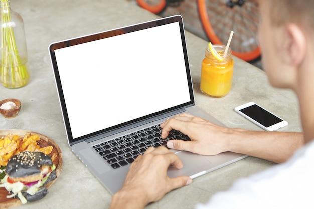 Bijgesneden schot van jonge freelancer met behulp van laptop voor werk op afstand, zittend aan cafe tafel met leeg scherm mobiele telefoon
