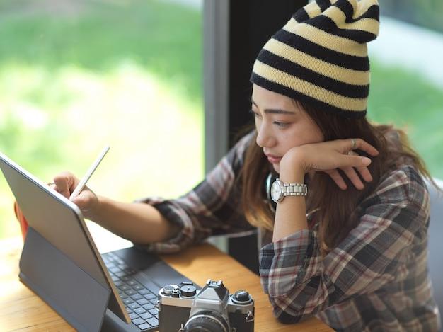 Bijgesneden schot van jonge vrouw die aan haar project werkt tijdens het schrijven op tablet