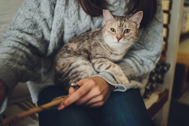 Bijgesneden schot van jonge vrouw met schattige cyperse kat in handen. Premium Foto