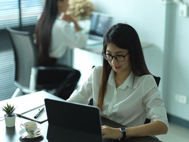Bijgesneden schot van jonge vrouwelijke beambte die met tablet werkt met haar collega op de achtergrond