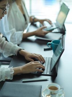 Bijgesneden schot van jonge vrouwelijke ondernemers team dat samen aan hun project in kantoorruimte werkt