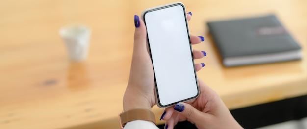 Bijgesneden schot van jonge vrouwelijke universiteitsstudent met smartphone