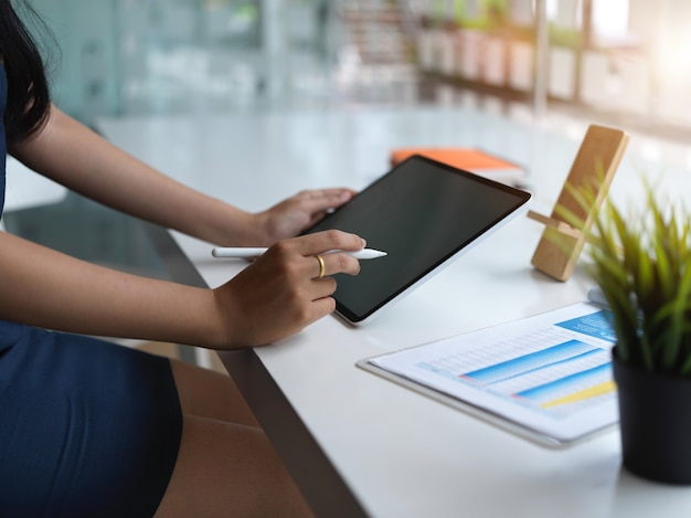 Bijgesneden schot van jonge zakenvrouw haar project met tablet in moderne kantoorruimte schaven