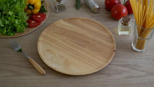 Bijgesneden schot van keukentafel met groenten op houten keukengerei en ingrediënten