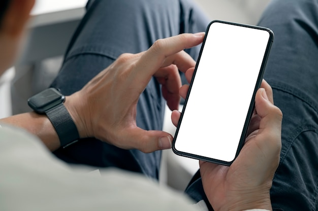 Bijgesneden schot van man handen met smartphone met leeg scherm zittend in de woonkamer thuis.