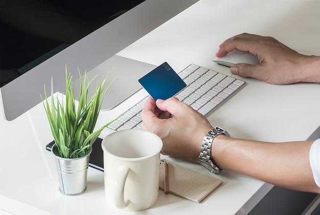 Bijgesneden schot van man met behulp van destop computer en creditcard te houden om online te kopen