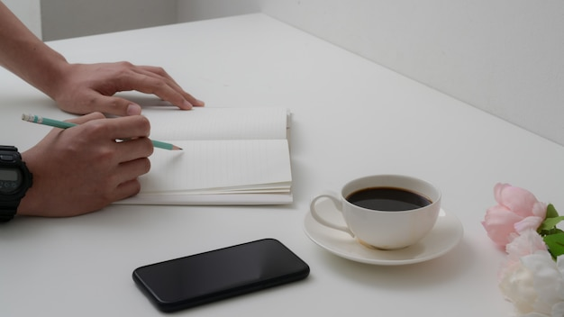 Bijgesneden schot van mannelijke universitaire student nemen korte notitie over notebook