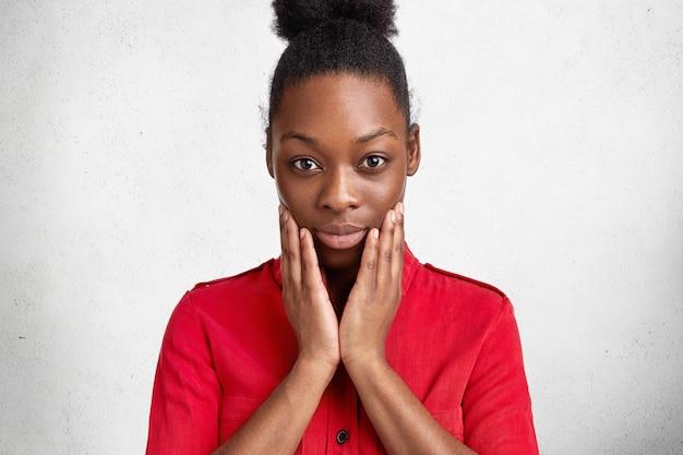 Bijgesneden schot van middelbare leeftijd afro-amerikaanse vrouw toont haar gezonde, zachte donkere huid na spa-procedure, wangen raakt, geeft om welzijn en schoonheid. aantrekkelijke ernstige vrouw binnen