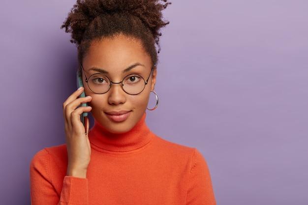Bijgesneden schot van mooie donkere vrouw heeft ernstige uitdrukking, draagt een ronde bril en coltrui, heeft een telefoongesprek, krijgt een interessante suggestie