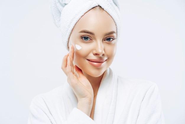 Bijgesneden schot van mooie jonge vrouw geldt crème voor verjonging, gezonde zachte huid, cosmetisch product gebruikt, toont mooi effect van bodylotion, draagt comfortabele zachte witte badjas, handdoek