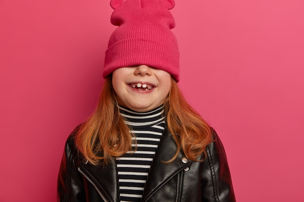 Bijgesneden schot van mooie kleine vrouwelijke kind verbergt onder hoed, heeft plezier alleen, glimlach toont in het algemeen witte melktanden, dromen om mannequin te worden draagt stijlvolle leren jas, grijnst van geluk