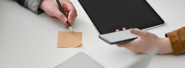 Bijgesneden schot van ondernemers samen te werken en het schrijven van een idee op kladblok